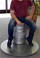 Grown man sitting on keg placed on Jaybird false bottom and stand